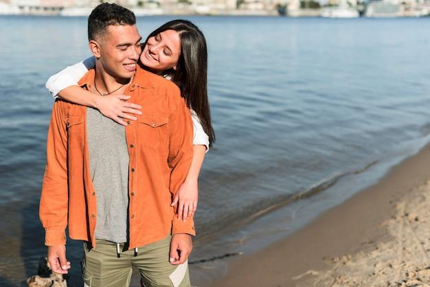 Vue de face du couple romantique posant ensemble à la plage