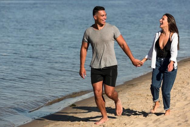 Vue de face du couple romantique se tenant la main tout en se promenant sur la plage
