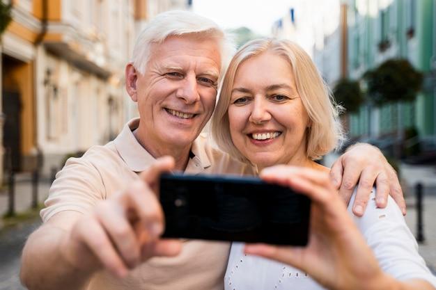 Vue de face du couple senior souriant à l'extérieur en prenant un selfie