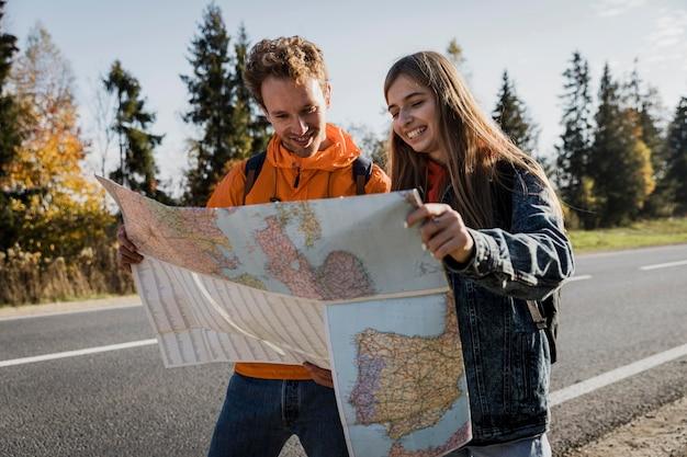 Vue de face du couple smiley consulting map lors d'un road trip