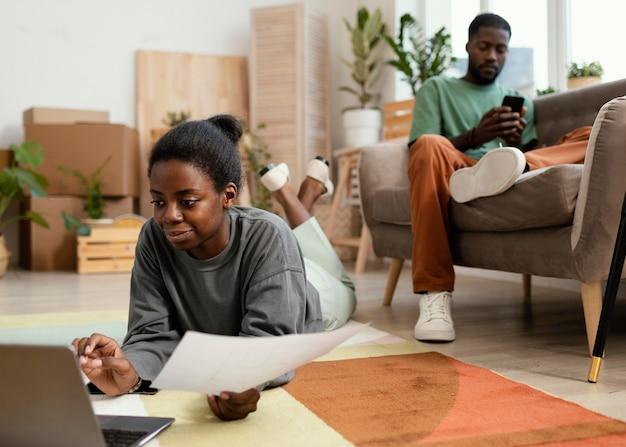 Vue de face du couple sur le sol faisant des plans pour redécorer la maison avec un ordinateur portable