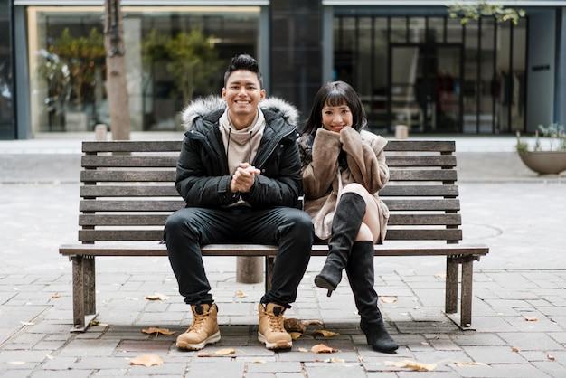 Vue de face du couple souriant assis sur un banc
