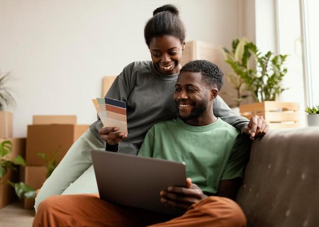 Vue de face du couple souriant sur le canapé faisant des plans pour redécorer la maison