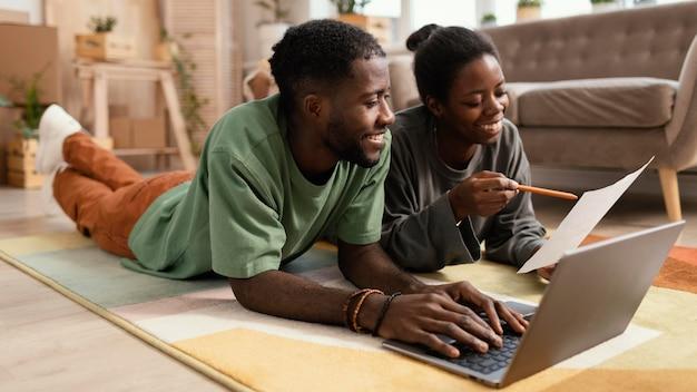 Vue de face du couple souriant à l'étage faisant des plans pour redécorer la maison avec un ordinateur portable