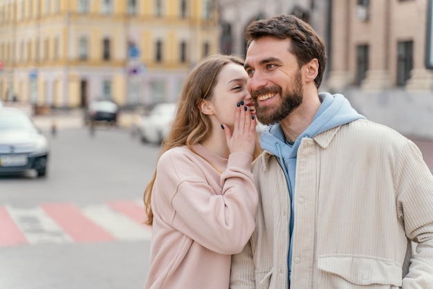 Vue de face du couple souriant à l'extérieur dans la ville