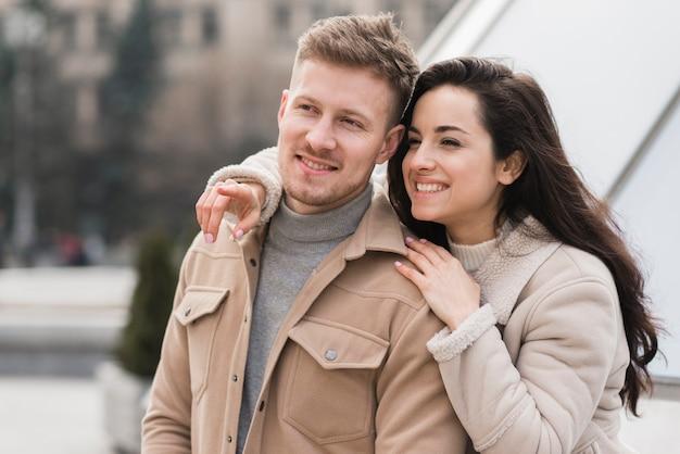 Vue de face du couple souriant à l'extérieur