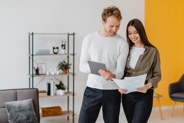 Vue de face du couple souriant faisant des plans pour reconditionner la maison ensemble