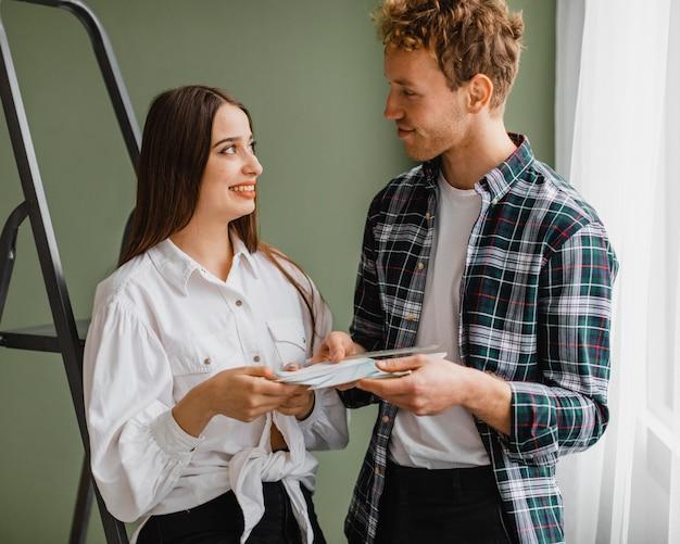 Vue de face du couple souriant faisant des plans pour redécorer la maison