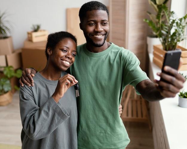 Vue de face du couple souriant prenant selfie dans leur nouvelle maison
