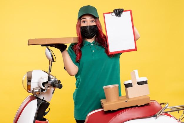 Vue de face du courrier féminin en masque avec café de livraison sur mur jaune