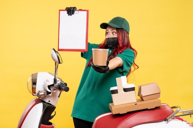 Vue de face du courrier féminin en masque avec livraison de café et de nourriture sur mur jaune