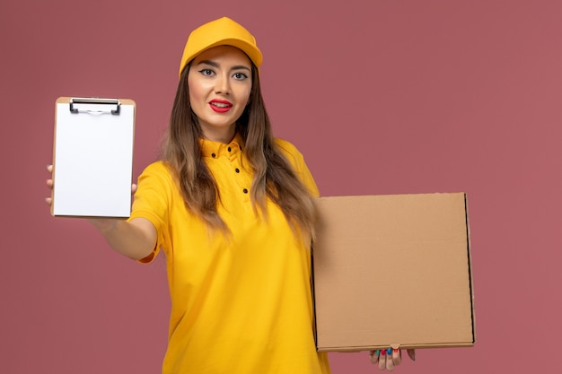 Vue de face du courrier féminin en uniforme jaune et cap holding food box et bloc-notes sur mur rose