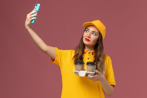 Vue de face du courrier féminin en uniforme jaune et cap tenant la livraison tasses à café prenant photo sur mur rose