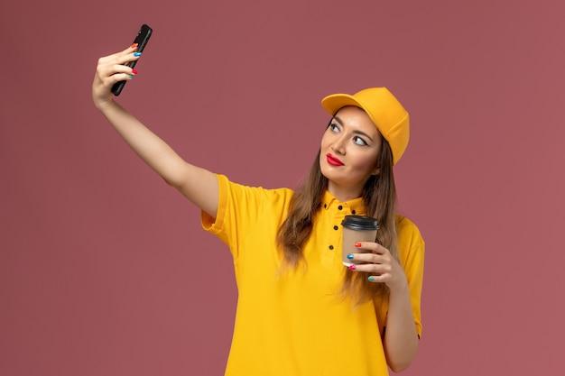 Vue de face du courrier féminin en uniforme jaune et cap tenant la tasse de café de livraison et prendre une photo sur le mur rose