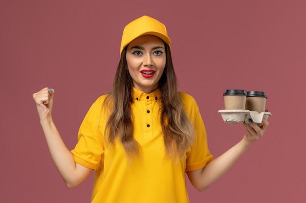 Vue de face du courrier féminin en uniforme jaune et cap tenant des tasses de café de livraison se réjouissant sur le mur rose