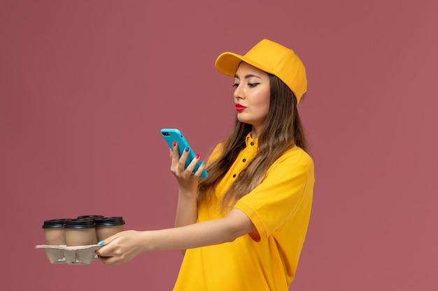 Vue de face du courrier féminin en uniforme jaune et cap tenant des tasses à café marron et prendre une photo sur un mur rose