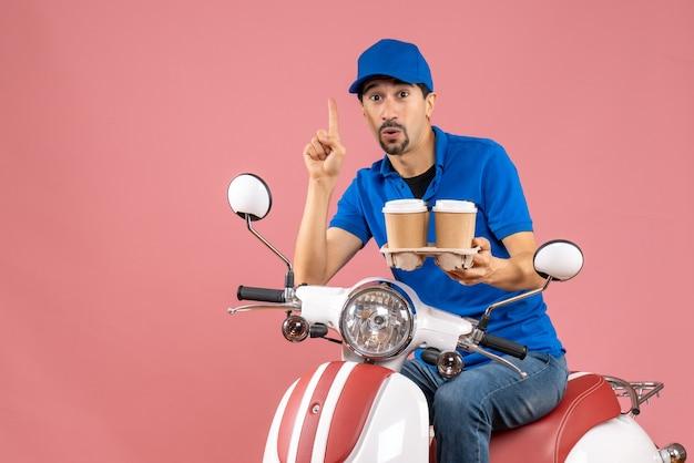 Vue de face du courrier homme portant un chapeau assis sur un scooter pointant vers le haut sur fond de pêche pastel