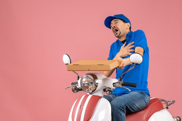 Vue de face du courrier homme portant un chapeau assis sur un scooter souffrant d'une crise cardiaque sur fond de pêche pastel