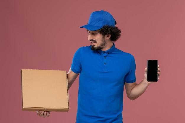 Vue de face du courrier masculin en chapeau uniforme bleu avec boîte de nourriture et téléphone sur ses mains sur le mur rose clair