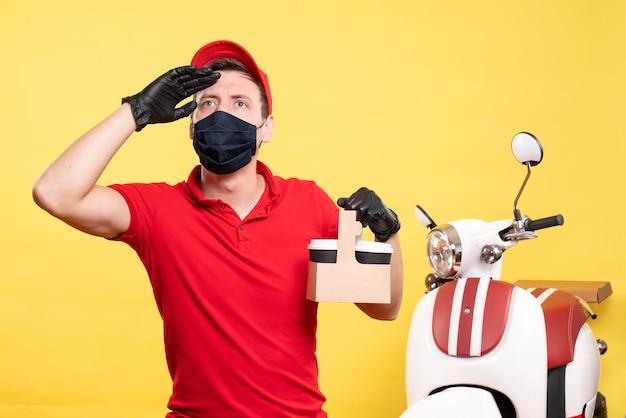 Vue de face du courrier masculin en masque noir avec des tasses à café sur un virus du travail jaune - service de travail uniforme des livreurs