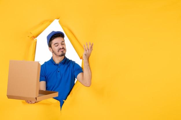 Vue de face du courrier masculin tenant une boîte à pizza ouverte sur un espace jaune
