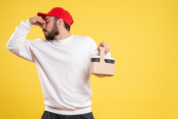 Vue de face du courrier masculin tenant le café de livraison et collant son nez sur le mur jaune