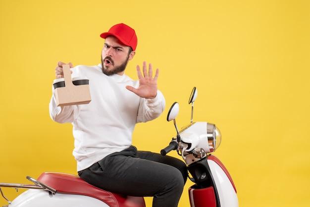 Vue de face du courrier masculin tenant le café de livraison sur le mur jaune