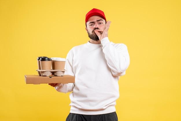 Vue de face du courrier masculin tenant la livraison de nourriture et de café sur le mur jaune