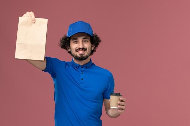 Vue de face du courrier masculin en uniforme bleu et capuchon avec tasse de café de livraison et paquet de nourriture sur ses mains sur le mur rose