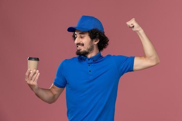 Vue de face du courrier masculin en uniforme bleu et capuchon avec tasse de café de livraison sur ses mains se réjouissant sur le mur rose