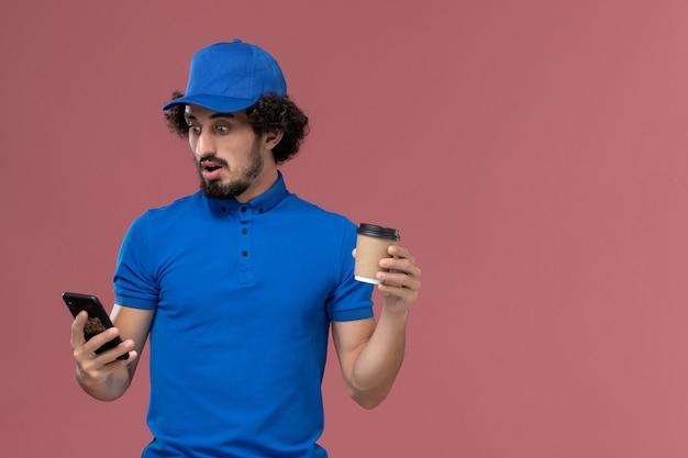Vue de face du courrier masculin en uniforme bleu et capuchon avec tasse de café de livraison et téléphone sur ses mains sur le mur rose
