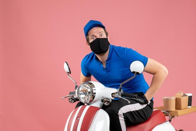 Vue de face du courrier masculin en uniforme bleu et des gants sur un travail de nourriture rose travail de restauration rapide couleur de vélo de livraison