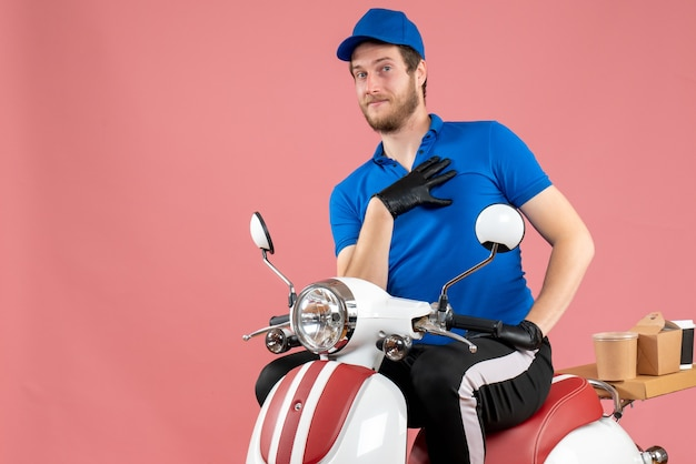 Vue de face du courrier masculin en uniforme bleu et des gants sur un vélo de livraison de nourriture de service de restauration rapide de couleur rose
