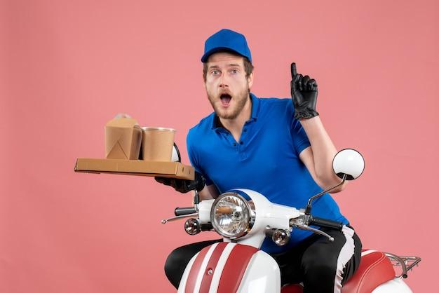 Vue de face du courrier masculin en uniforme bleu tenant une boîte de café et de nourriture sur un service de couleur de vélo de travail de restauration rapide rose