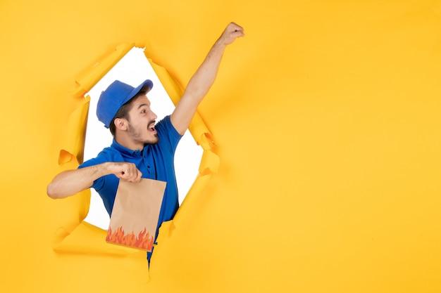 Vue de face du courrier masculin en uniforme bleu tenant un emballage de nourriture dans une pose de superman sur un espace jaune