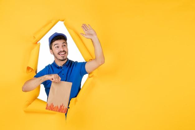 Vue de face du courrier masculin en uniforme bleu tenant un emballage de nourriture sur un espace jaune