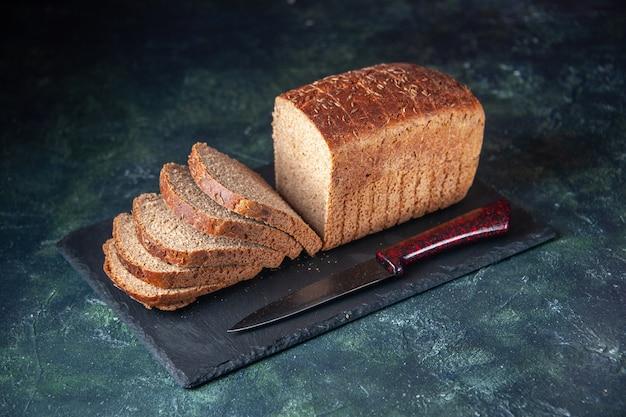 Vue de face du couteau à tranches de pain noir sur une planche de couleur foncée sur fond de couleurs mélangées en détresse