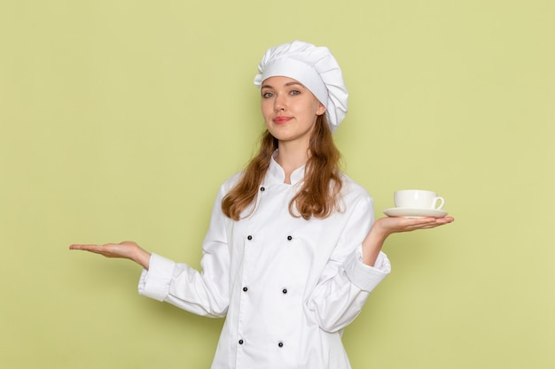 Vue de face du cuisinier en costume de cuisinier blanc souriant et tenant une tasse blanche avec du café sur le mur vert