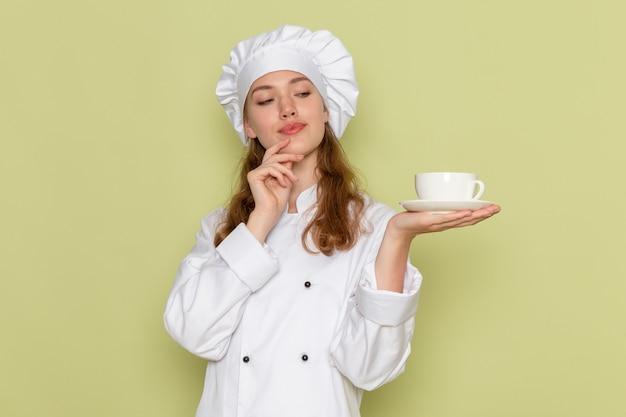 Vue de face du cuisinier en costume de cuisinier blanc tenant une tasse de café sur le mur vert