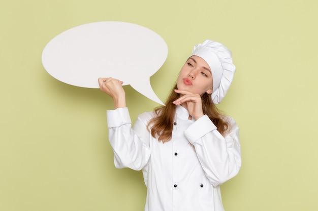 Vue de face du cuisinier féminin portant un costume de cuisinier blanc tenant une grande pancarte et penser au mur vert