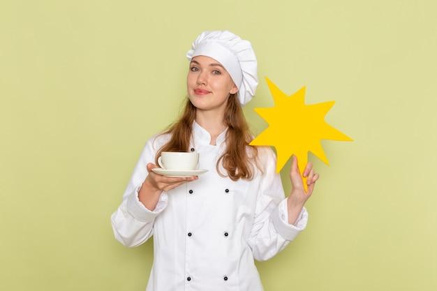 Vue de face du cuisinier femme portant costume de cuisinier blanc tenant une pancarte jaune avec une tasse de café sur le bureau vert cuisine cuisine cuisine repas couleur femelle