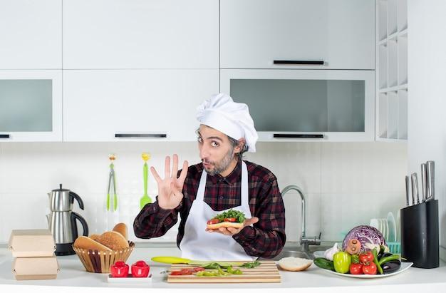 Vue de face du cuisinier masculin brandissant un délicieux hamburger debout derrière la table de la cuisine