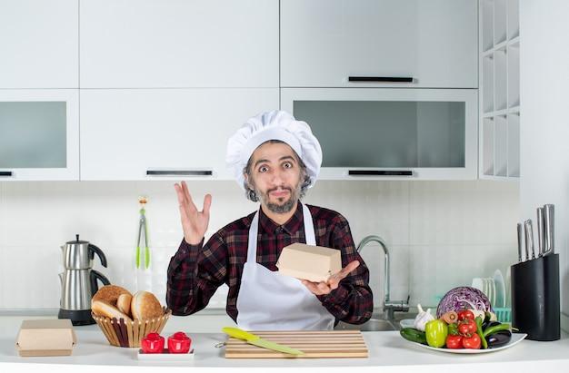 Vue de face du cuisinier masculin tenant une petite boîte debout derrière la table de la cuisine dans la cuisine
