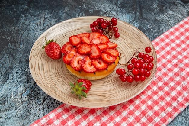 Vue de face du délicieux gâteau avec des fraises fraîches sur une surface grise