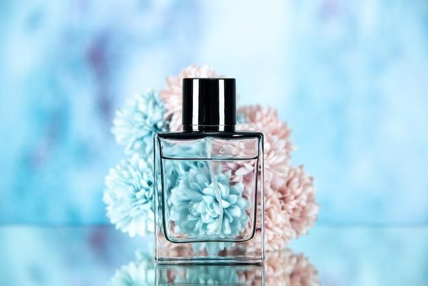 Vue de face du flacon de parfum rectangle et des fleurs sur bleu flou
