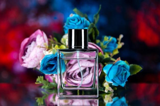 Vue de face du flacon de parfum rectangle fleurs colorées sur résumé rouge bleu foncé