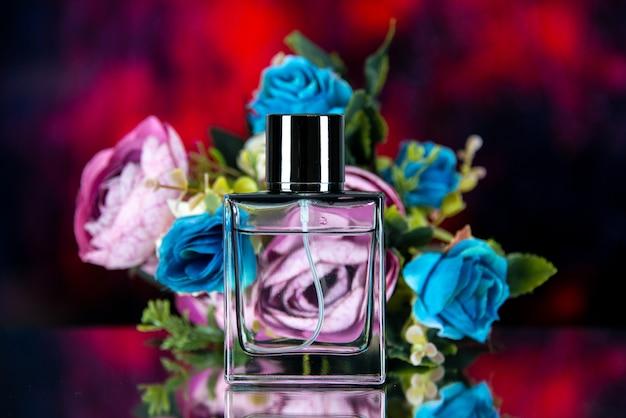 Vue de face du flacon de parfum rectangle fleurs colorées sur résumé rouge foncé