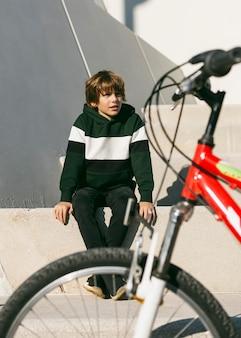 Vue de face du garçon au parc avec son vélo