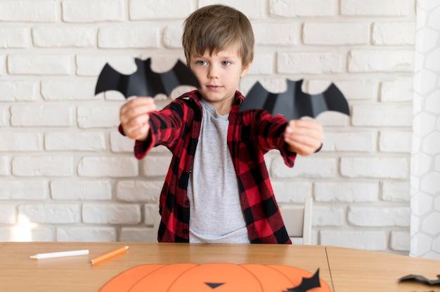 Vue de face du garçon avec chauve-souris en papier