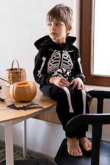 Vue de face du garçon en costume de squelette